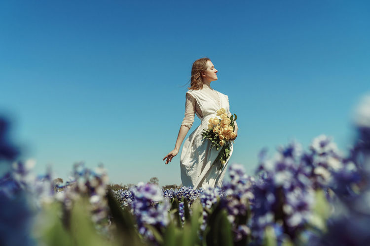 Woman standing by flowering plant against blue sky