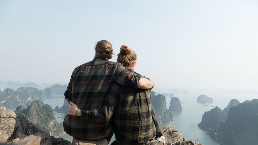 Rear View Of Couple Sitting On Rocks Against Sky