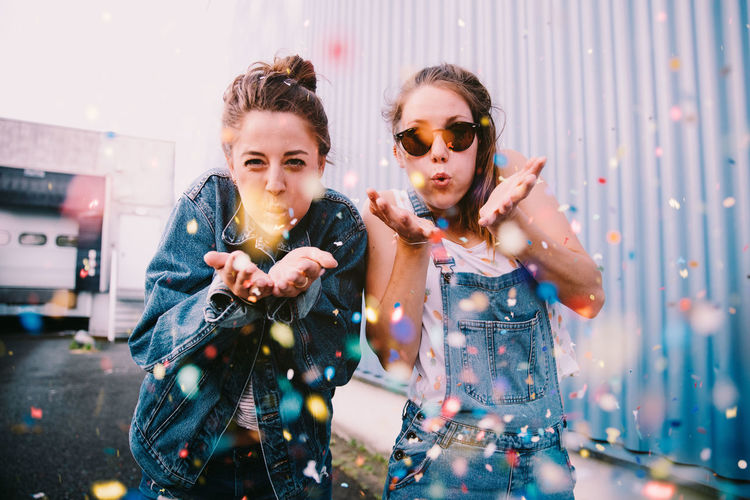Portrait of young women blowing confetti while standing outdoors
