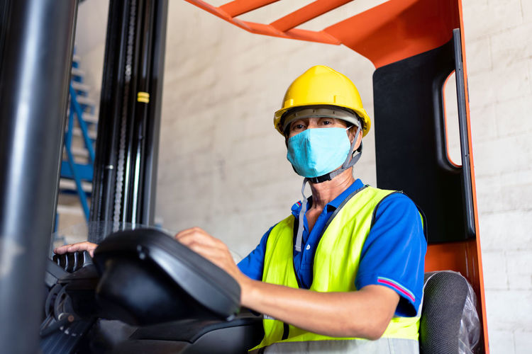 Portrait of worker wearing hardhat and mask