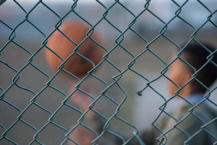 Close-up of chainlink fence with boy spinning basketball in background