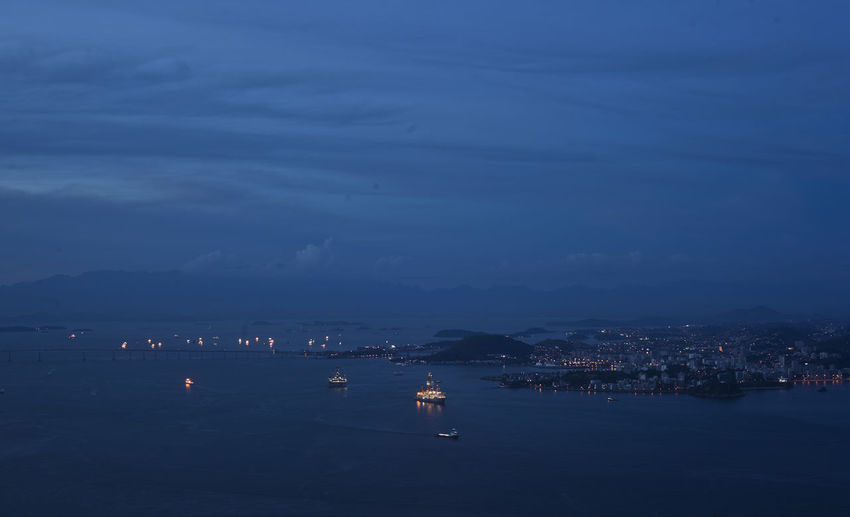 Sailboats In Sea By City Against Sky At Night