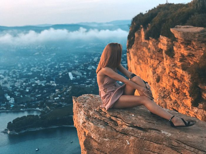 Woman relaxing on cliff against townscape