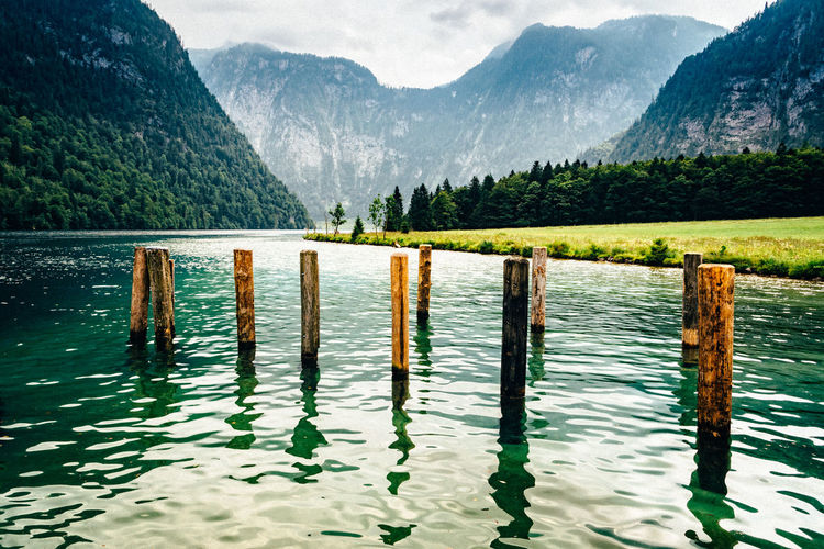Scenic view of Konigssee Water Beauty In Nature Tranquility Scenics - Nature Tranquil Scene Nature Day No People Tree Non-urban Scene Plant Outdoors Königssee Lake Scenics Scenery Landscape Nature Pier Mountain Mountain Range Idyllic Wood - Material Post Wooden Post