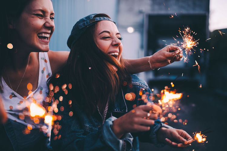 Happy Friends Enjoying While Holding Sparklers