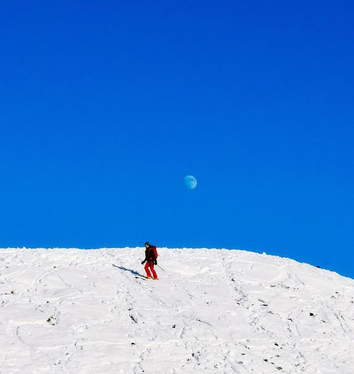 Full length of person on snowcapped mountain against clear blue sky
