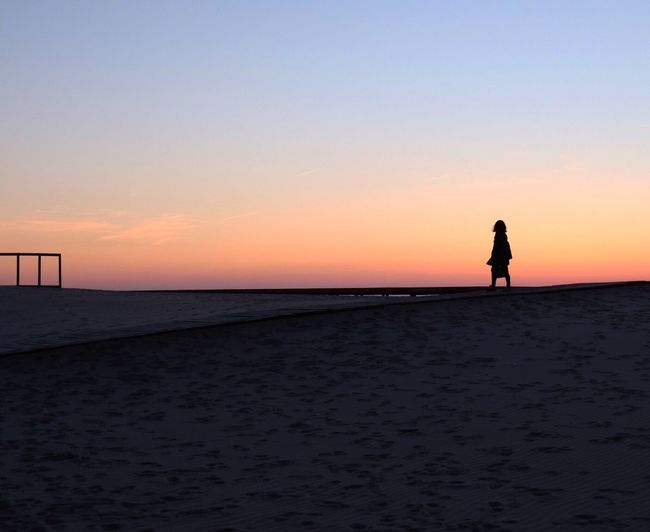 Silhouette man standing on beach against clear sky during sunset
