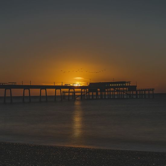 Pier over sea against clear sky at sunset