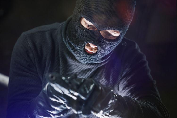 Portrait of burglar holding gun
