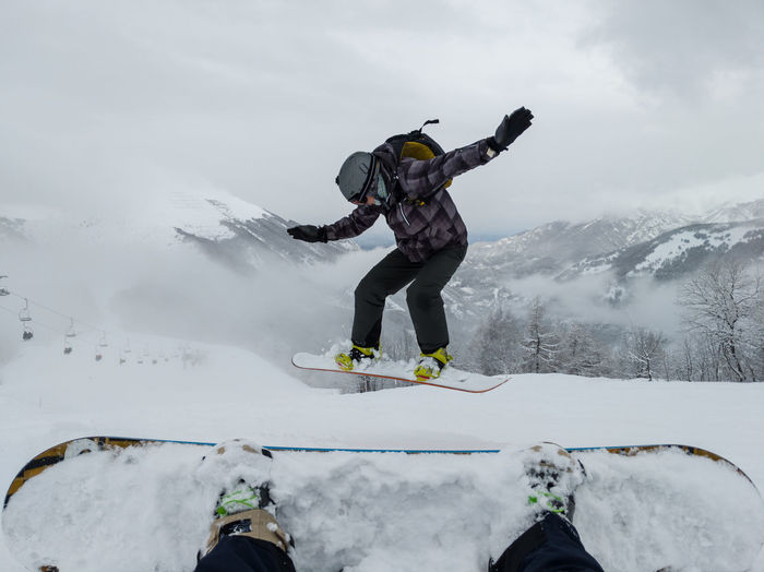 Man snowboarding over land against cloudy sky