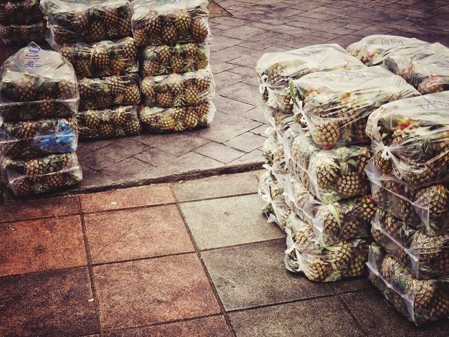 Pineapple in the wrap Pineapple Plastic Wrap Wrapped Wrap No People Day Sunlight High Angle View Nature Outdoors Shadow Footpath Street Large Group Of Objects Still Life
