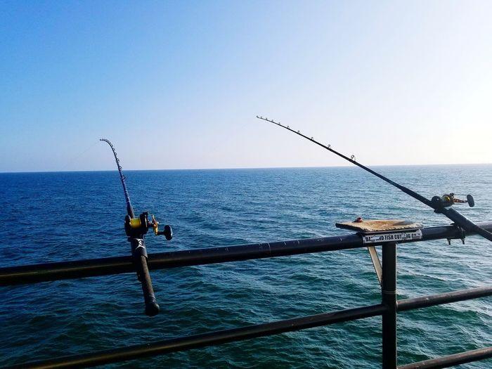Fishing rod on sea against clear blue sky