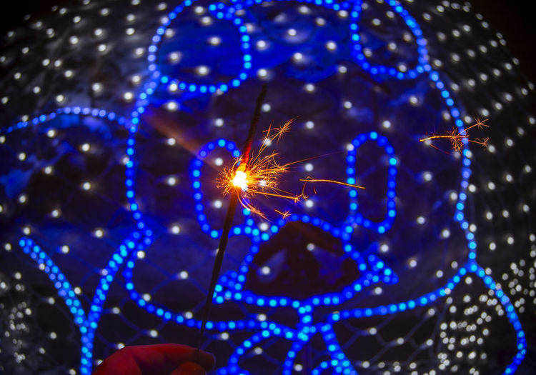 Illuminated Blue Night Close-up Glowing Celebration Human Hand Lighting Equipment Focus On Foreground Holding Hand Selective Focus Arts Culture And Entertainment Human Body Part Light Body Part Sparkler Finger Christmas Decoration Christmas Lights Neon Pig Light And Shadow Christmas Blue Background