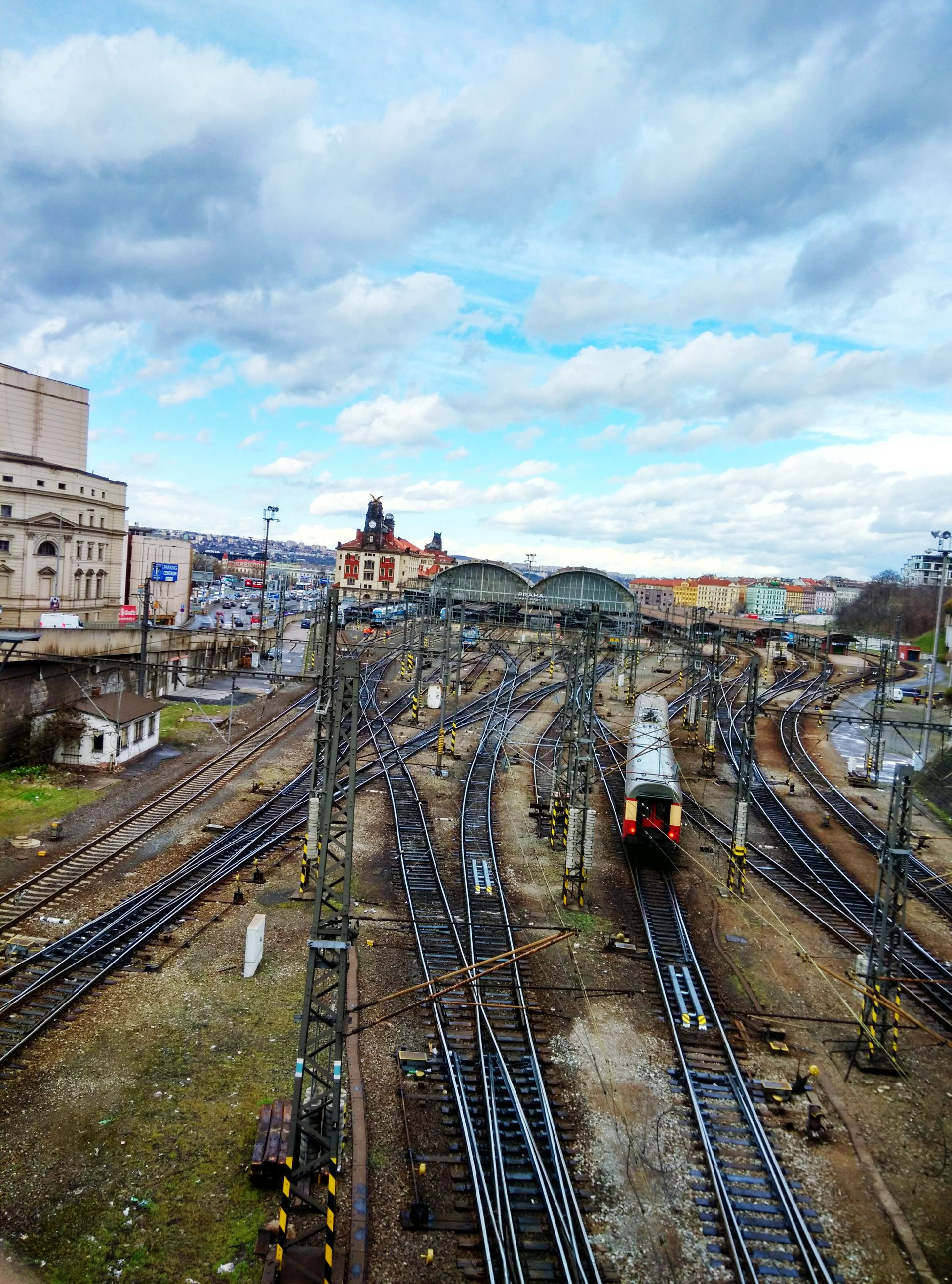 railroad track, transportation, building exterior, architecture, built structure, high angle view, city, rail transportation, public transportation, sky, cloud - sky, railroad station, mode of transport, city life, the way forward, diminishing perspective, railroad station platform, vanishing point, cityscape, travel