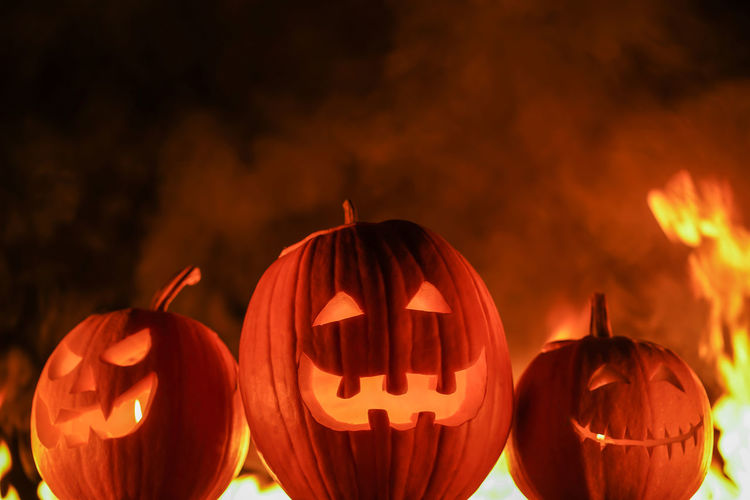 Illuminated jack o lanterns with fire in background at night