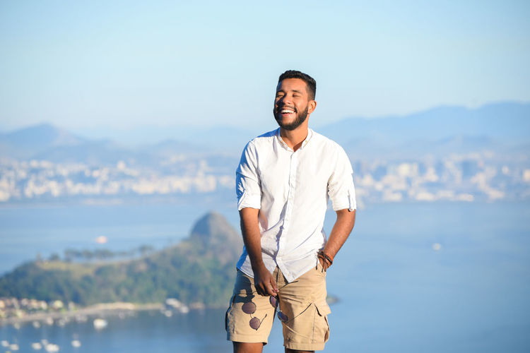 Smiling Young Man Standing Against Sea
