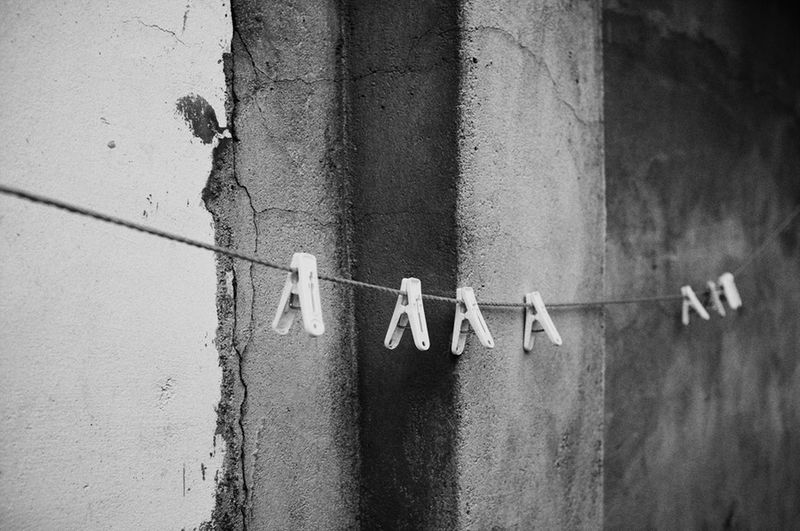 Clothespins Hanging On String By Wall