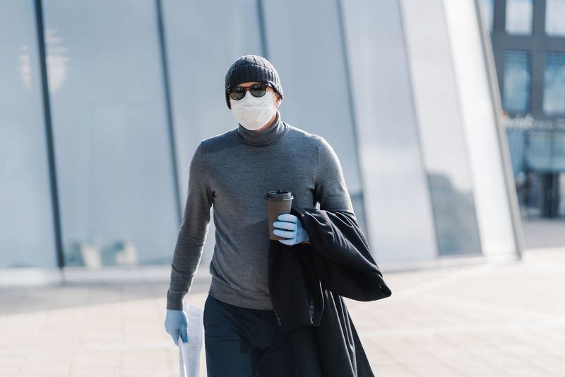 Man wearing mask holding coffee cup and newspaper in city