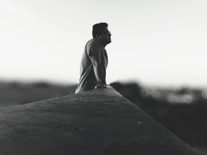 Side View Of Man Leaning Against Railing