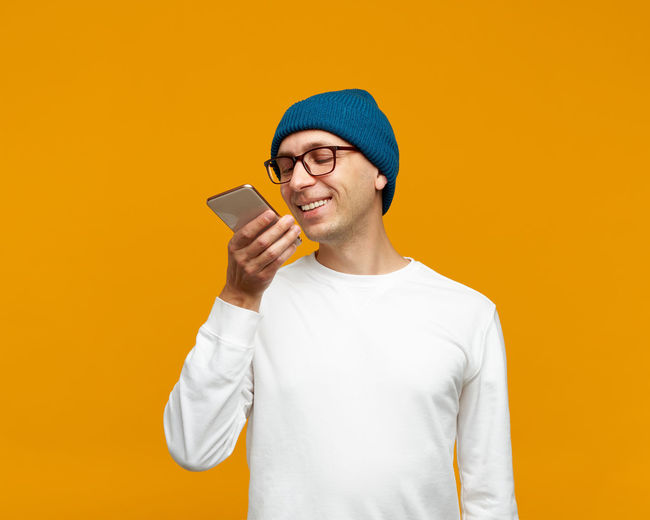 Mid adult man using mobile phone against yellow background