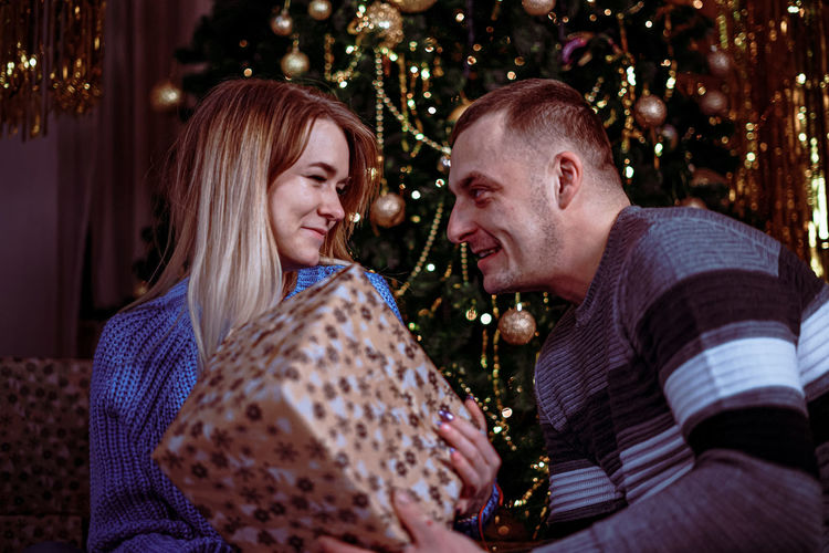 Young man and woman in christmas tree