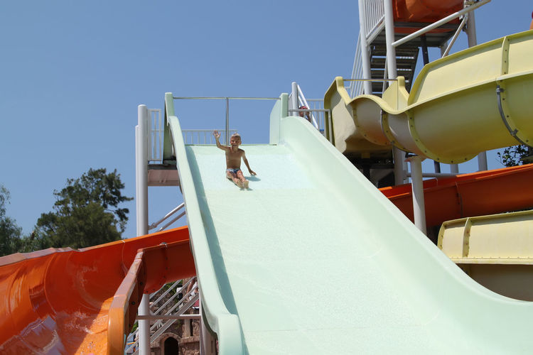 Low angle view of boy sliding at water park