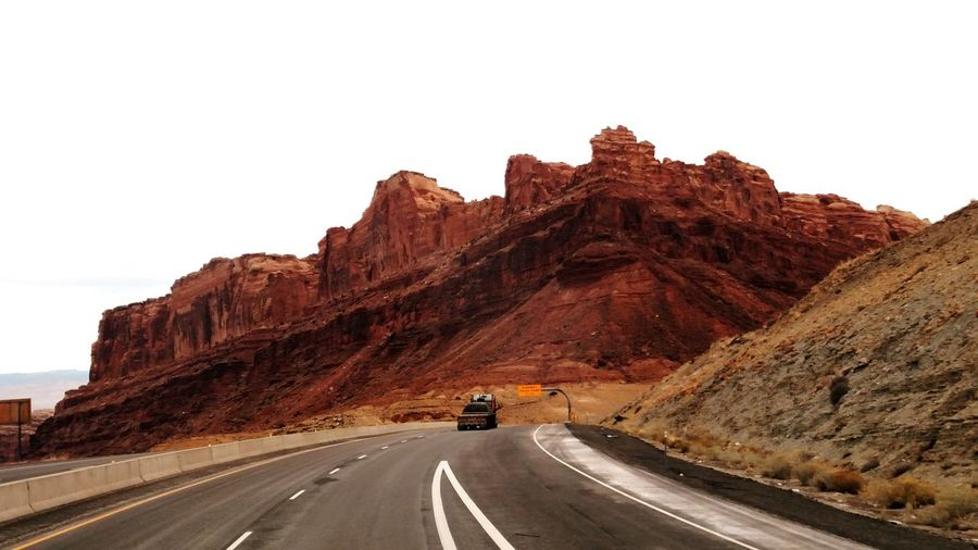 Truck On Road Against Rocky Mountains
