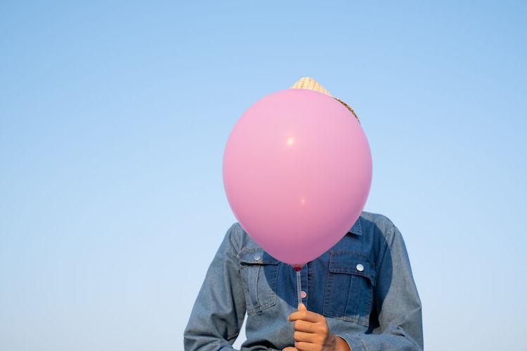 Midsection of woman holding balloons against blue sky