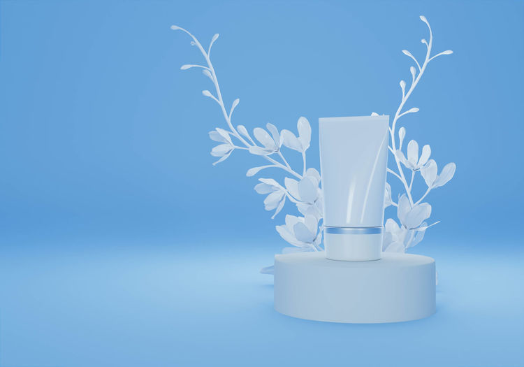 Close-up of vase on table against blue background