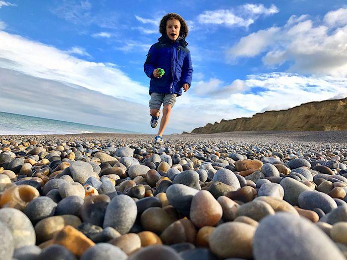 Boy running on the beach, pebble beach, child running. Beach Day Boy Running Boy Cloud - Sky Sky Full Length One Person Child Childhood Leisure Activity Beach Pebble