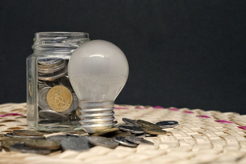 Close-up of coins and light bulb on table against black background