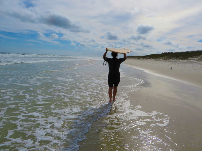 Woman walking on beach carrying surfboard above her head. Active Lifestyle  Aged 40-45 Beach Cloud - Sky Full Length Horizon Over Water Leisure Activity Lifestyles Rear View Sand Scenics Sea Shore Sky Standing Surfboard Surfing Tranquil Scene Tranquility Walking Water Woman