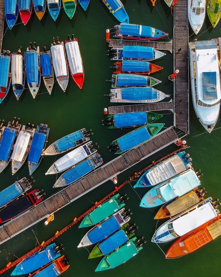 High angle view of multi colored boats moored at harbor in lake