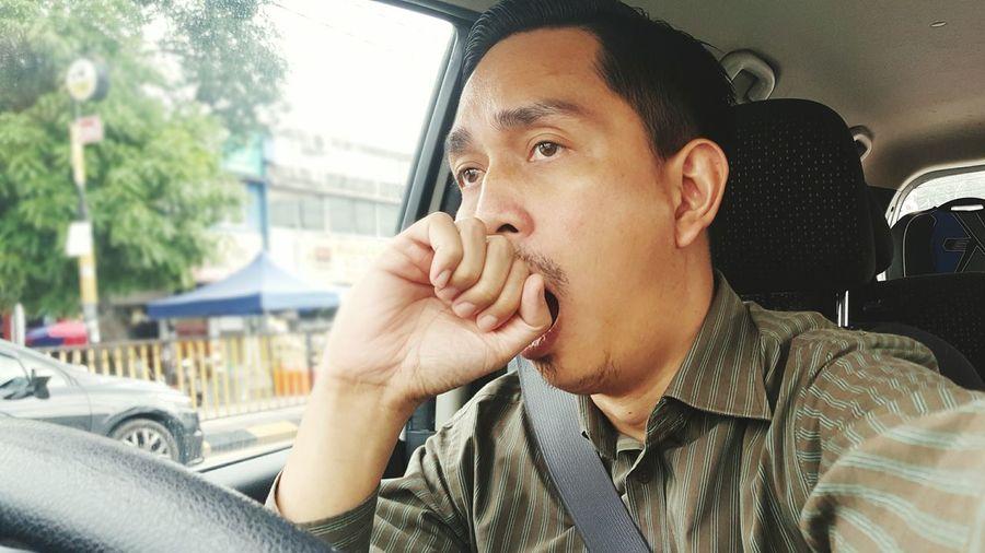 Tired man yawning while driving car