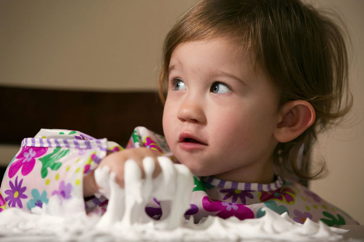Cute girl looking away while playing with foam on table