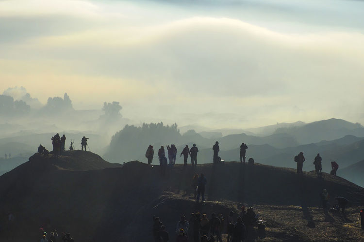 Silhouette People Standing On Mountain Peak During Foggy Weather