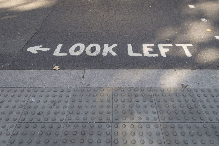 Pedestrian crossing with markings look left on the road to help tourist to look at the right direction before crossing the road London Streetphotography Pedestrians Sign Pedestrian Crossing Warning Sign Look Left Pavement Street High Angle View Sign Road Outdoors Footpath