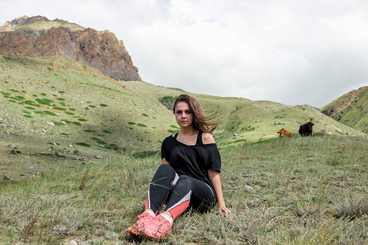 Portrait of young woman sitting on field against sky