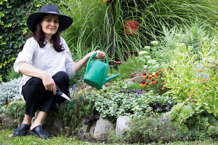 Portrait of smiling woman holding watering can and scissors by plants