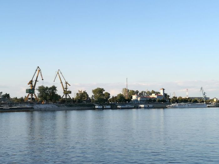 Commercial dock by sea against clear sky