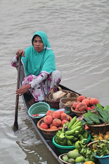 Woman selling food on boat in lake
