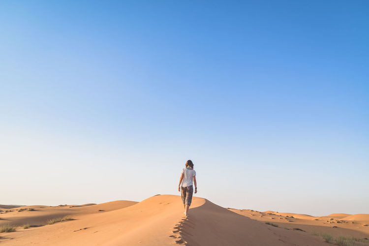 Adventure Arid Climate Clear Sky Desert Desert Desert Beauty Dry Full Length Leisure Activity Lifestyles Oman One Person Outdoors Sand Sand Dune Sunny Travel Travel Destinations Travel Photography Women Young Adult Young Women