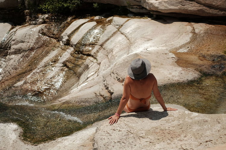 Rear view of woman wearing bikini while sitting on rock