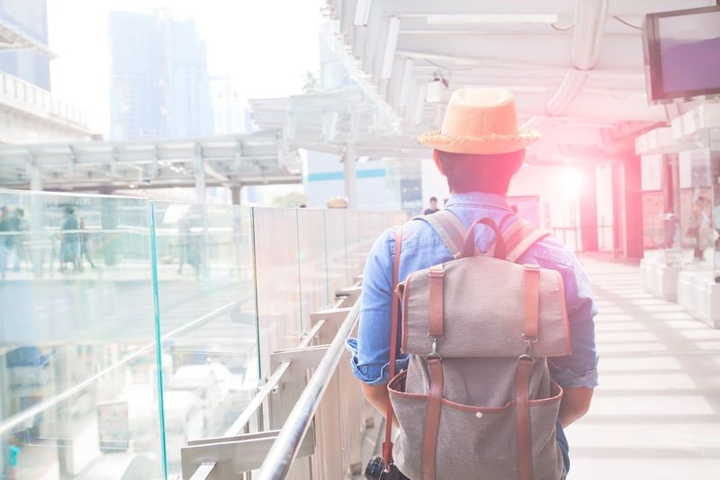 Asian backpacker walking on modern walk way in city, Travel and Lifestyle concept Architecture ASIA Asian  Building Exterior Built Structure City Day Men One Person Outdoors People Real People Rear View Standing Sunlight Tourist Traveler Walking Young Adult