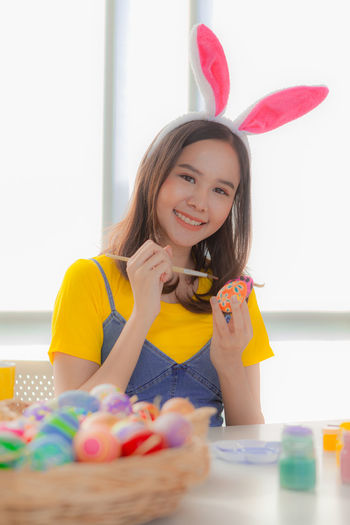 Portrait of smiling woman decorating easter egg