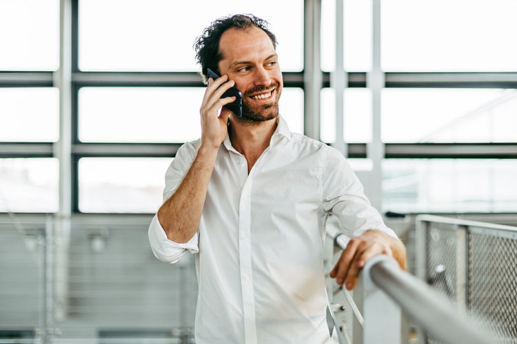 smiling caucasian man on the phone Technology One Person Talking Using Phone Telephone Smiling Standing Communication Waist Up Happiness Front View Men Holding Wireless Technology Males  Mobile Phone Adult Connection Indoors  Looking Mature Adult Mature Men Man Caucasian Smile