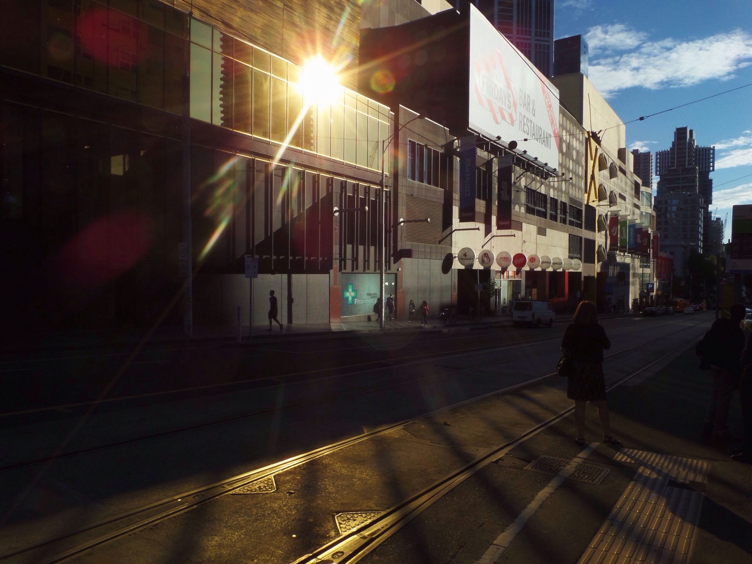 building exterior, architecture, built structure, city, city life, street, transportation, silhouette, walking, men, sunlight, building, lifestyles, illuminated, sky, full length, city street, road