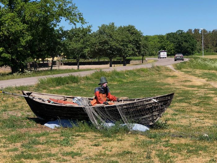 Doll in boat on field against trees