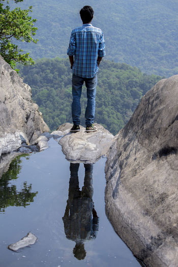 Rear view of man standing on rock by water