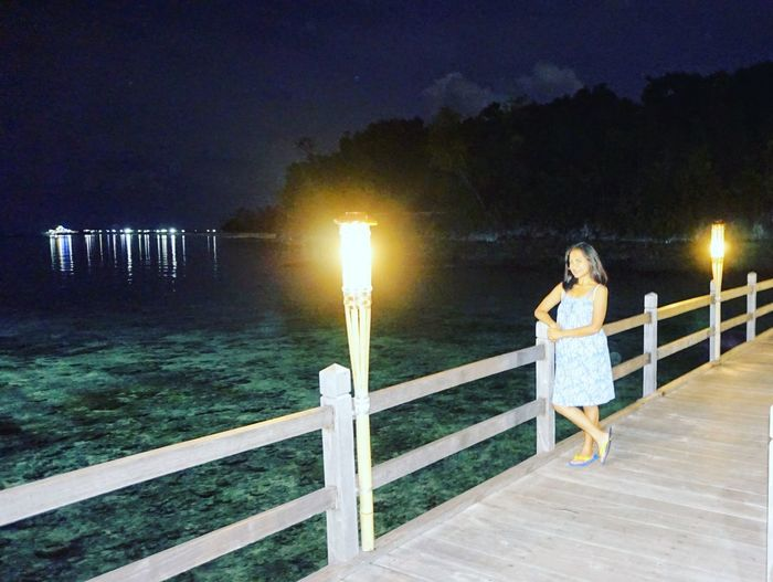 Woman standing by railing against sky at night